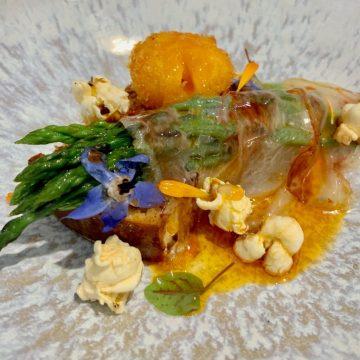 Espargos Selvagens servidos sobre brioche caseiro com papada de porco, maionese de espargos, gema de ovo frita, pipocas de chouriço e óleo de chouriço